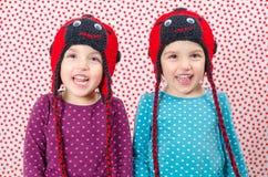 Tvilling- flickor ler på kameran och är lyckliga Liten chi Arkivbild