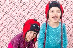 Tvilling- flickor ler på kameran och är lyckliga Liten chi Royaltyfri Foto