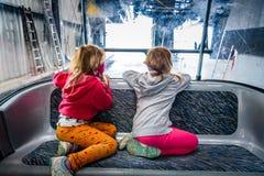 Tvilling- flickor som rider kabinkabelbilen och tycker om sikten Royaltyfria Bilder