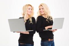 Tvilling- hållande bärbara datorer för vänlig attraktiv blond syster Arkivbild
