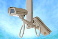 Tvilling- kamera för säkerhet som isoleras på bakgrund för blå himmel Arkivbilder