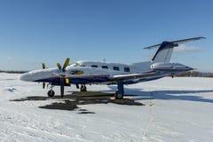 Tvilling- motorflygplan med turbopropmotorkraftverket under insnöad solig vinterdag arkivbild