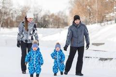Tvilling- pojkar som går i vintern, föräldrar går tillbaka arkivfoton