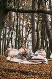 Tvilling- syster som läser en bok på en gunga i hösten f Arkivbild