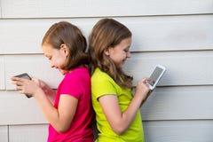 Tvilling- systerflickor som spelar med minnestavlaPC:n som är lycklig på den vita väggen royaltyfria bilder