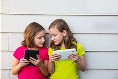 Tvilling- systerflickor som spelar med minnestavlaPC:n som är lycklig på den vita väggen royaltyfri fotografi