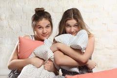 Tvilling- systrar med kuddar i sovrummet Arkivfoto