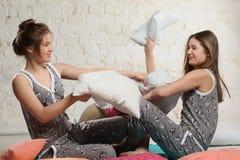 Tvilling- systrar med kuddar i sovrummet Royaltyfri Bild