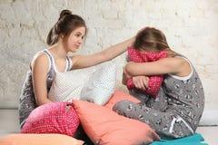 Tvilling- systrar med kuddar i sovrummet Arkivfoton