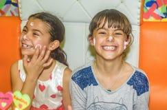 Tvilling- systrar på födelsedagberöm med kakan Arkivbild