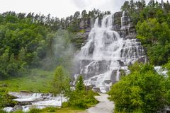 Tvindefossen Waterfall is a gorgeous 152m waterfall near Voss tumbling in strands with a graceful character. Tourism, popular, stock photography
