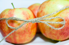 Tvinna binder upp closeupen för tre äpplen Arkivfoto