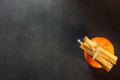 Tvinnar kanelbruna pinnar för tangerin som binds med, på svart kort för hälsning för nytt år för bakgrundsjul Arkivbild