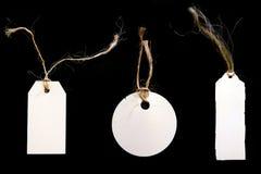 tvinnar svarta etiketter för bakgrund white Arkivfoto
