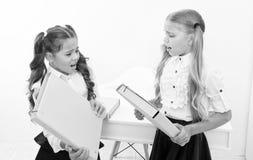Tvist av flickor för små ungar slåss med mappar i klassrum Gräla eller tvist av små ungar i skola arkivfoto