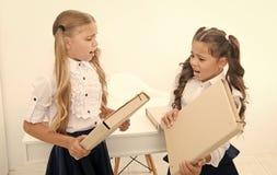 Tvist av flickor f?r sm? ungar sl?ss med mappar i klassrum Gr?la eller tvist av sm? ungar i skola arkivfoto