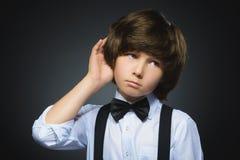 Tvivel, uttryck och folkbegrepp - pojke som tänker över grå bakgrund fotografering för bildbyråer