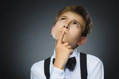 Tvivel, uttryck och folkbegrepp - pojke som tänker över grå bakgrund royaltyfri bild