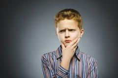 Tvivel, uttryck och folkbegrepp - pojke som tänker över grå bakgrund arkivbild