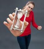 Tvivelaktig härlig ung kvinna som rymmer en timme glass mot spänning Royaltyfri Foto