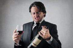 Tvivelaktigt affärsman med ett exponeringsglas och en flaska av vin Royaltyfri Foto