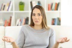 Tvivelaktigt kvinna som hemma rycker på axlarna skuldror Arkivfoton