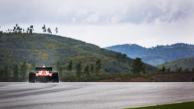 Tävlings- bil i landskap av kullar med sprej av regn Arkivbilder
