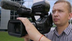TVoperatören tar bort videoen med en yrkesmässig videokamera, som står på en tripod Panoramaskytte stock video