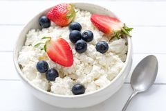 Tvorog, agricoltori formaggio, ricotta o ricotta in ciotola bianca con le bacche fresche di estate Immagini Stock
