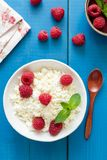 Tvorog, cottage cheese or ricotta with raspberries. Ricotta with raspberries in a bowl on blue wooden background. Curd cheese, cottage cheese, tvorog. Healthy Stock Image