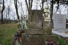 TVRDOMESTICE SLOVAKIEN - 12 3 2016: Gravar, gravstenar och kors på traditionell kyrkogård Staty av en ängel på den gamla gravvalv Arkivfoto