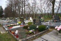 TVRDOMESTICE SLOVAKIEN - 12 3 2016: Gravar, gravstenar och kors på traditionell kyrkogård Votive stearinljus lykta och blommor Arkivfoto