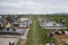 TVRDOMESTICE SLOVAKIEN - 12 3 2016: Gravar, gravstenar och kors på traditionell kyrkogård Votive stearinljus lykta och blommor Fotografering för Bildbyråer