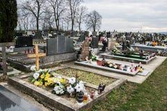 TVRDOMESTICE SLOVAKIEN - 12 3 2016: Gravar, gravstenar och kors på traditionell kyrkogård Votive stearinljus lykta och blommor Royaltyfri Foto