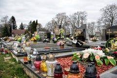 TVRDOMESTICE SLOVAKIEN - 12 3 2016: Gravar, gravstenar och kors på traditionell kyrkogård Votive stearinljus lykta och blommor Arkivbild