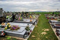 TVRDOMESTICE SLOVAKIEN - 12 3 2016: Gravar, gravstenar och kors på traditionell kyrkogård Votive stearinljus lykta och blommor Royaltyfri Bild