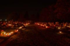 TVRDOMESTICE SLOVAKIEN - 2 11 2015: Votive stearinljus lyktabränning på gravar i kyrkogård på nattetid all helgdagsafton hallows Arkivbilder