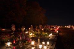 TVRDOMESTICE SLOVAKIEN - 2 11 2015: Votive stearinljus lyktabränning på gravar i kyrkogård på nattetid all helgdagsafton hallows Fotografering för Bildbyråer