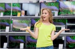 Молодая женщина смотрит ТВ в магазине стоковое фото