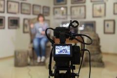 TVskytte på museet Lcd-bildskärm på camcorderen Flickan framme av kameran Ett rekord av intervjun arkivfoto