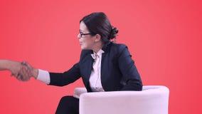 TVstudion Closeup av brunetten i exponeringsglas Hon sitter i studion i en affärsdräkt och intervjuer Röd bakgrund arkivfilmer