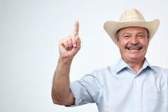Twój reklama tutaj Pracowniany portret przystojny starszy mężczyzna w błękitnej koszula i kowbojskiego kapeluszu seansu kopii prz zdjęcia stock
