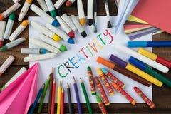 Twórczości pojęcie kolorowy papier, kredka, kolorowy ołówek i papier z słowem twórczość -, Zdjęcie Royalty Free