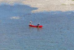 Tw paddlers die een rode kano duwen Stock Foto's