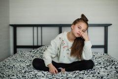Twaalf éénjarigen leuk meisje die pret in haar ruimtezitting hebben op het bed Portret royalty-vrije stock foto's