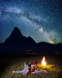 Twain-Liebhaber, die unglaublich schönen sternenklaren Himmel und Milchstraße bewundern und nahe dem Feuer nachts liegen Lizenzfreies Stockbild