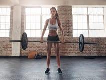 Twarda młoda kobieta ćwiczy z barbell Zdjęcia Stock