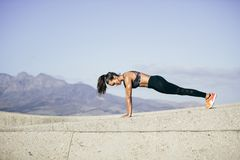 Twarda młoda kobieta robi pushups outdoors Obraz Stock