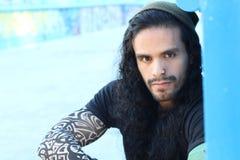 Twardy przyglądający latynoski mężczyzna z długie włosy i tatuażami zdjęcia stock