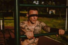 Twardy tatuujący mężczyzna opiera na treningu barze outside fotografia royalty free